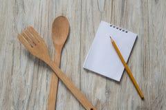木匙子和小铲有笔记本和铅笔的在木背景 库存图片