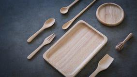 木匙子和板材在深灰石膏在桌面上 免版税图库摄影