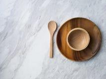 木匙子和板材在白色大理石 库存照片