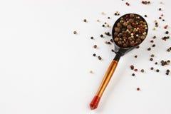 木匙子用在白色的干胡椒 免版税图库摄影