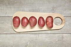 木匙子用香芹籽和迷迭香,土豆,葱,在木背景的大蒜 顶视图 库存图片
