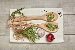 木匙子用香芹籽和迷迭香,葱,在木背景的大蒜 顶视图 免版税库存照片