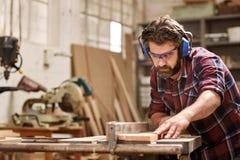 木匠与切开一个木板条的机械一起使用 免版税库存图片