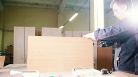 木匠与在工作凳的一把电螺丝刀一起使用在工厂,固定的家具细节 股票视频