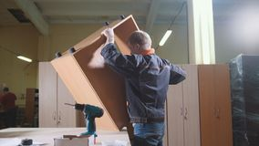 木匠与在工作凳的一把电螺丝刀一起使用在工厂,固定的家具细节 免版税库存图片