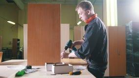 木匠与在工厂的一把电螺丝刀一起使用,固定的家具细节 股票录像