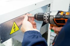 木匠与在金属设备的一把电螺丝刀一起使用 小心危险标志 定调子与阳光 免版税库存照片