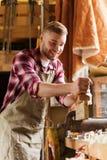 木匠与飞机和木头一起使用在车间 免版税库存照片