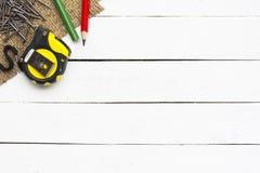 木匠业工具例如与木铅笔和钉子的卷尺在木白色背景 房子的设备 免版税库存照片