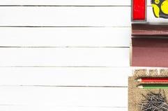 木匠业工具例如与木铅笔和钉子的卷尺在木白色背景 房子的设备 库存图片
