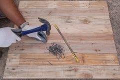 木匠业锤子大头钉和木头地板框架设计背景 免版税库存照片
