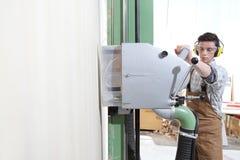 木匠人工作在木匠业里,切开了与垂直的圆锯机器的一个木盘区,保护与耳朵笨拙的人 库存照片