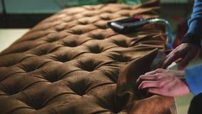 木匠修理在使用家具订书机的沙发身体的织品 股票视频