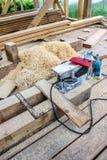 木匠切开与电锯的木头的` s工具在建造场所 免版税库存照片