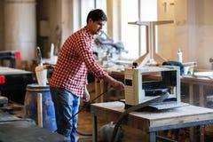 木匠厚度整平机清洗了使用空气喷气机,木匠的商店 图库摄影