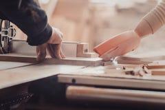 木匠在木材加工工作机械工具 工作在木材加工机器的木匠在木匠业商店 免版税图库摄影