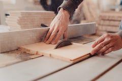 木匠在木材加工工作机械工具 工作在木材加工机器的木匠在木匠业商店 免版税库存照片