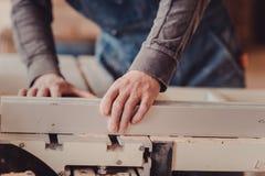 木匠在木材加工工作机械工具 工作在木材加工机器的木匠在木匠业商店 免版税库存图片