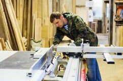 木匠在木材加工机器的工作有一把圆锯的 免版税库存图片