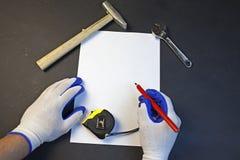 木匠在纸片画、锤子铅笔卷尺和一把板钳在黑背景 图库摄影