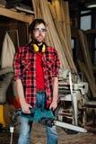 木匠在车间锯与一个电锯的树 在锯切过程中的木匠 免版税库存图片