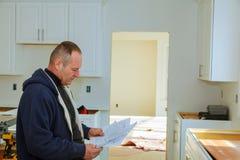 木匠工作保留安装厨柜的一个计划 免版税库存照片