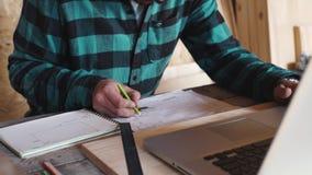 木匠工作在他的车间用制图仪、纸、统治者、铅笔和膝上型计算机 影视素材