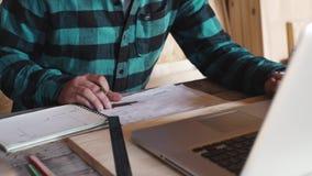 木匠工作在他的车间用制图仪、纸、统治者、铅笔和膝上型计算机 股票录像