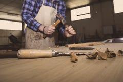 木匠工具 凿子或蛾眉凿木头的在工作在工作凳的木匠 木匠业车间 库存照片