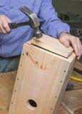 木匠插入鸟舍的底部 免版税库存照片