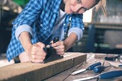 木匠涉及木头在一个家庭车间,木头计划的刨床板条  免版税库存照片