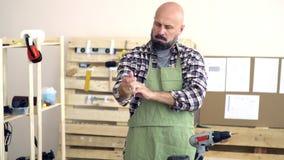 木匠白种人出现,秃头和与一个胡子,与一严厉的查寻和卷他的格子衬衫袖子  影视素材