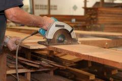 木匠的手与一把圆锯一起使用在木匠业车间 免版税库存图片