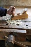 木匠的手在有飞机的木匠业车间 免版税库存照片