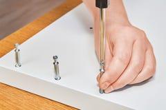 木匠的手拧紧家具联合连接器螺栓 库存图片