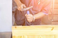木匠的手有凿子的在手上 库存图片