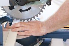在工作场所的安全有通报锯和手的 库存图片