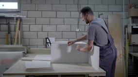 木匠装配一个衣橱,固定被处理的颗粒盘使用手钻,扭转螺丝 股票录像