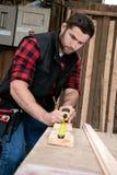 木匠,测量,操练和做木材产品的木工作者工作 库存图片