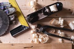 木匠,盖屋顶的人的工具的顶视图,为木材加工 飞机,角落,钢丝钳,手套,从研磨机的驱动在a 库存照片