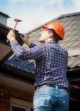 木匠画象在修理屋顶的工作 免版税库存照片