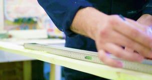 木匠` s概略的坚固性手和残破的手指钉子特写镜头,使用的铅笔和标记老木把柄的正方形a 股票视频