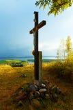 木十字架坐在日落的小山与 免版税库存照片