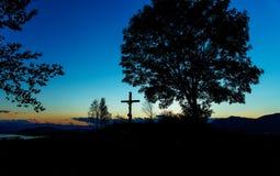 木十字架坐在日落的小山与 库存照片
