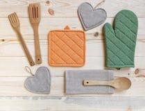 木厨房器物、握持热锅的布垫子、手套和餐巾在木t 免版税图库摄影
