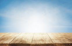 木台式背景,在蓝天的空的木书桌 免版税库存照片