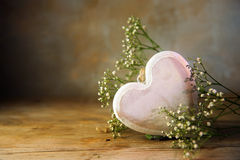 从木和白花的明亮的桃红色心脏反对一温暖vi 库存图片