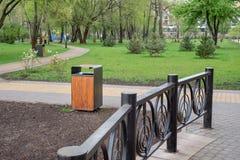 木和金属垃圾桶在公园 库存图片