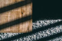 木咖啡桌和长毛绒地毯与阴影从阳光 图库摄影