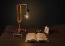 木在地板、手工制造铜管子灯、书、水瓶、cigaretta立场和打火机上 库存照片